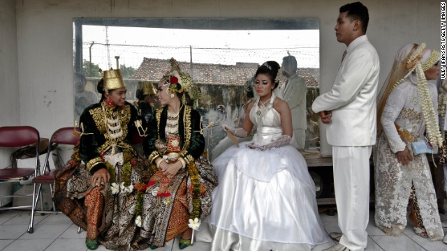 Bride and groom couples prepare for marriage during a mass wedding ceremony on December 12, 2012 in Yogyakarta, Indonesia. Twelve couples participated in a mass wedding as that day saw a surge in marriage across the globe to mark the once in a century date of 12/12/12.