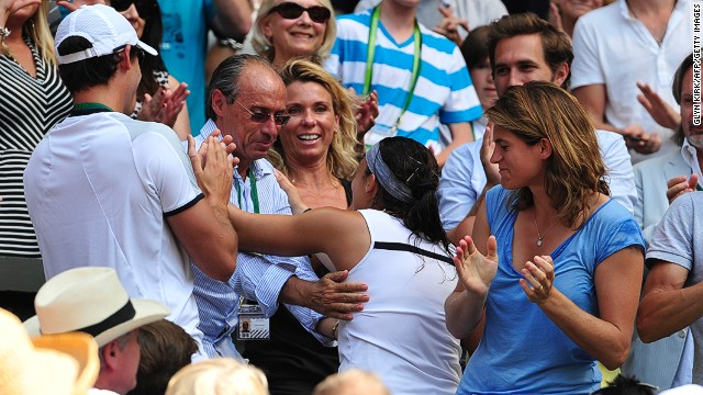 Bartoli embraces her father and former coach Walter. Her current coach, Amelie Mauresmo (right) was the last French winner of the Wimbledon women's singles title.