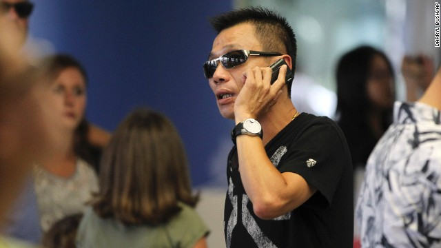 Kevin Cheng talks on his phone as he waits in the terminal after Asiana Airlines Flight 214 crash-landed on July 6. He said he was supposed to pick up students who were on board the flight from Seoul.