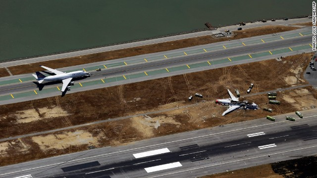 A plane sits on the runway on July 6 while emergency crews tend to the crash site.