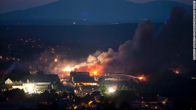 Firefighters battle fires in Lac-Megantic on July 6.