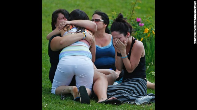 People cry and hug each other on July 7 while they sit on the grass at the Polyvalente Montignac, the school sheltering the people who were forced to leave their houses.