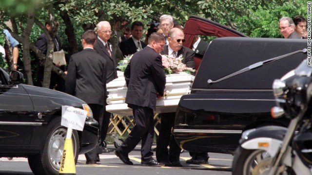 One of the children's caskets is put into a hearse after the funeral.