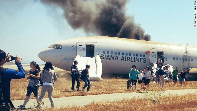Several passengers can be seen escaping Asiana Airlines flight 214 with their carry-on luggage.