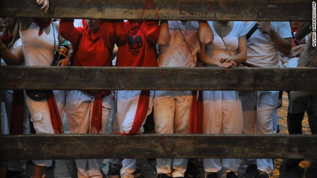 Revelers wait to watch the running of the bulls in the early morning on July 9.