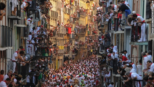 People watch the festivities from balconies on July 7. The annual event has become a popular symbol of Spanish culture, attracting thousands of tourists a year.