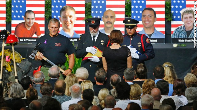 An honor guard presents a family member with an American flag during a memorial service in Prescott Valley, Arizona, on Tuesday, July 9. Nineteen members of the Granite Mountain Hotshots died Sunday, June 30, battling the Yarnell Hill wildfire.