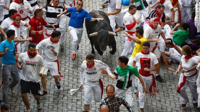 Revelers run alongside a bull in the streets on Wednesday, July 10.