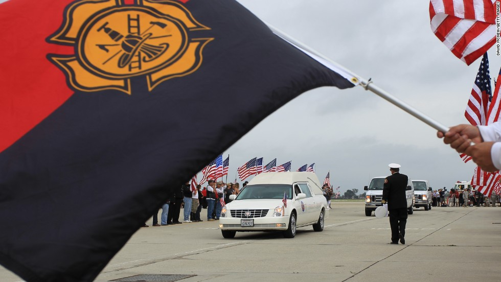 A hearse carrying the body of Christopher MacKenzie arrives at Los Alamitos Air Field, California, on July 10. MacKenzie was one of the <a href='http://www.cnn.com/interactive/2013/07/us/yarnell-fire/index.html'>19 firefighters</a> who lost their lives when they became trapped and their position overrun by flames from the Yarnell Hill Fire, southwest of Prescott on June 30.