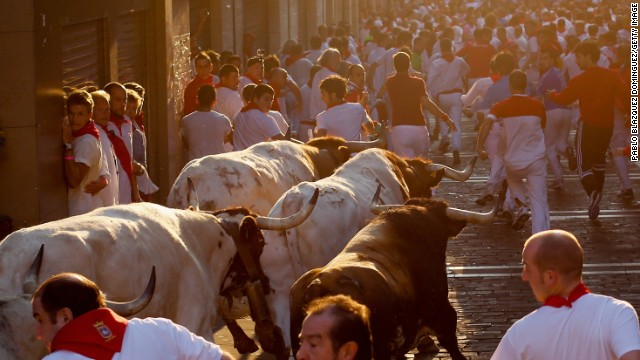 Revelers run with fighting bulls on July 11.
