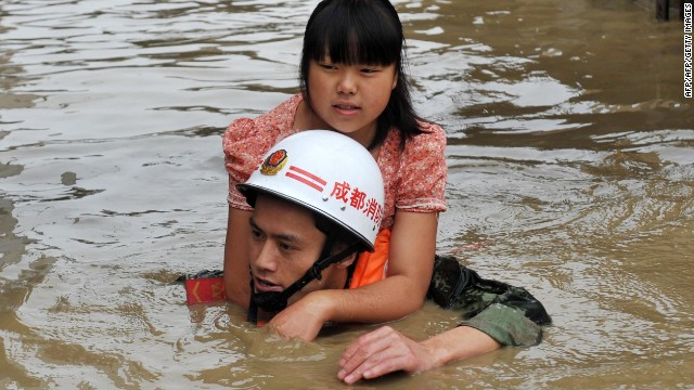 A rescuer helps a woman escape the floodwaters of the Tuo on July 11.