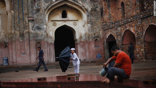 A young Muslim boy folds an umbrella in New Delhi on July 12.
