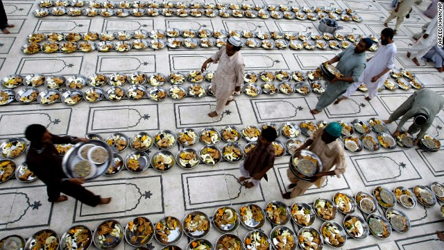 Volunteers arrange food to break the fast at a local mosque in Karachi, Pakistan, on Thursday, July 11.