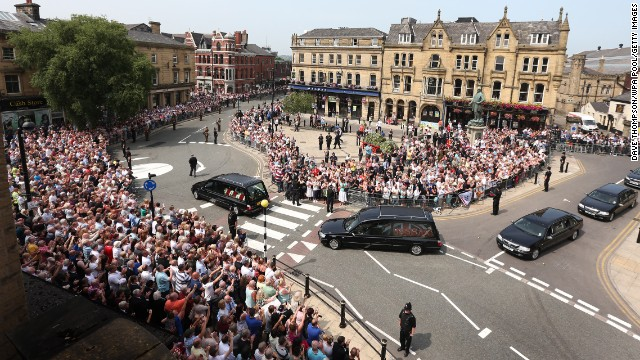 People line the streets to watch the funeral procession as it drives away from the church on July 12, in Bury, England.
