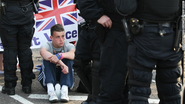 A man sits next to riot police in Belfast on July 13.