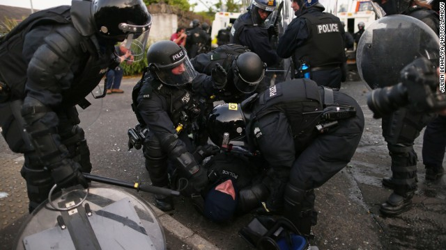Riot police help an injured officer as they try to contain protesters on Friday, July 12.