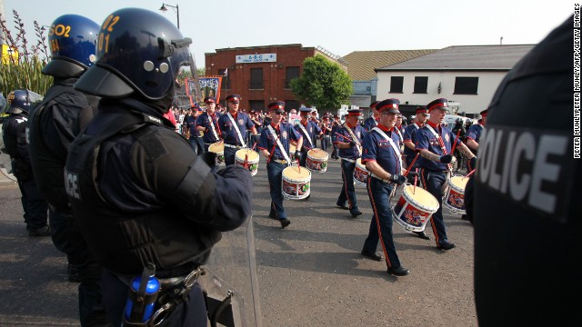 Police stand guard as Protestant Orangemen march in Belfast on July 12.