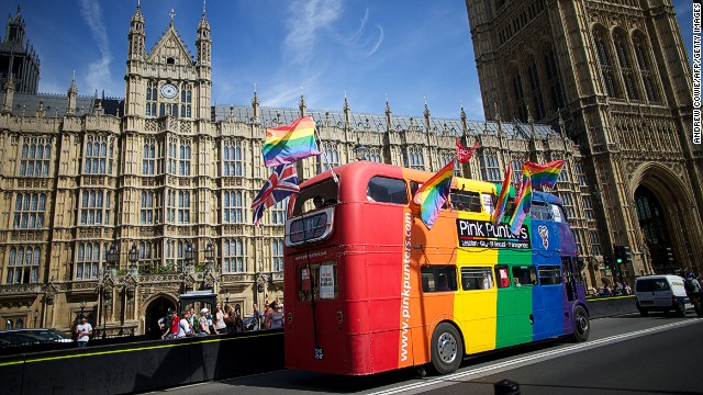 Gay campaigners drive a bus past the Houses of Parliament.