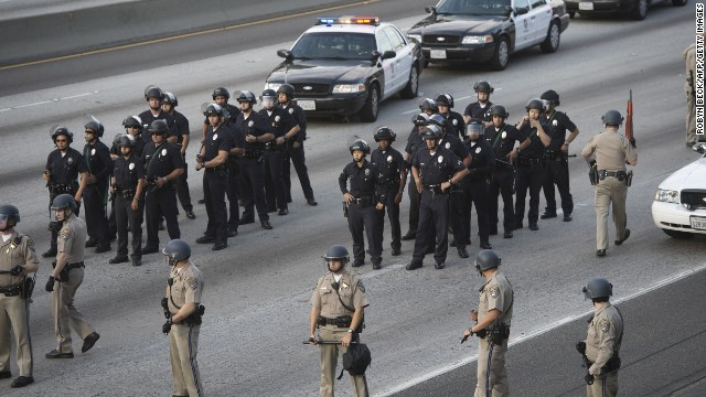 Police hold positions on I-10 in Los Angeles. Protesters walked onto the freeway, stopping traffic, on July 14.