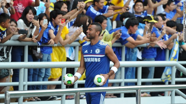 Ashley Cole throws footballs to excited fans during a Chelsea training session at Rajamangala Stadium in Bangkok, Thailand.
