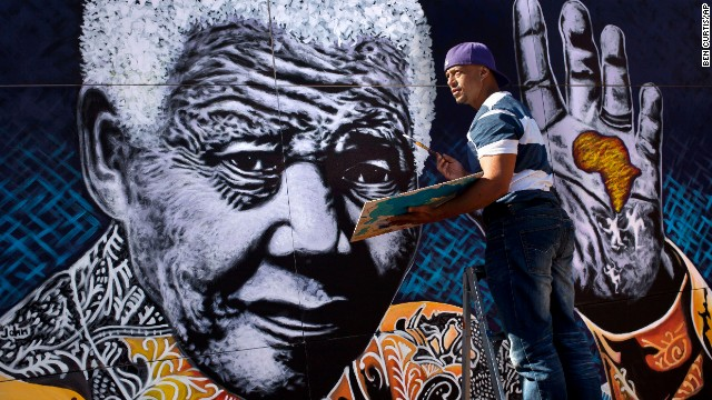 "South African artist John Adams works on a giant painting of Nelson Mandela in a suburb of Johannesburg. Mandela, an anti-apartheid icon and Nobel peace laureate, endured 27 years in prison before becoming South Africa's first democratically elected president. Click through the gallery for other artistic tributes to ""the world's most famous political prisoner."""