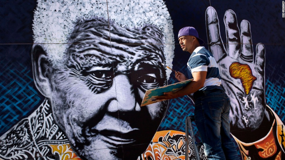 "South African artist John Adams works on a giant painting of <a href='http://www.cnn.com/2012/12/11/world/africa/nelson-mandela---fast-facts'>Nelson Mandela</a> in a suburb of Johannesburg. Mandela, an anti-apartheid icon and Nobel peace laureate, endured 27 years in prison before becoming South Africa's first democratically elected president. Click through the gallery for other artistic tributes to ""the world's most famous political prisoner."""