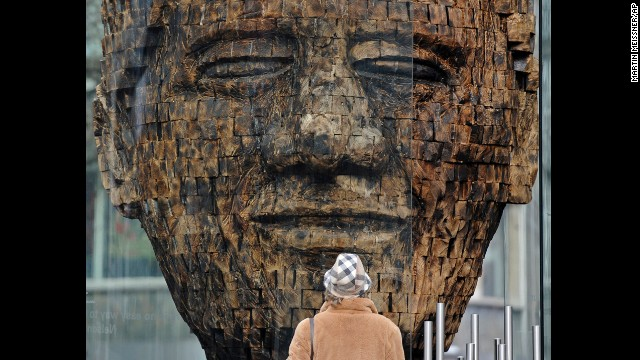 GERMANY: A woman views a giant wooden head of Mandela in the city center of Essen in western Germany. Created by artist Jems Robert Koko Bi from the Ivory Coast, the sculpture is made of burned spruce wood and is supposed to stand for the fight for freedom.