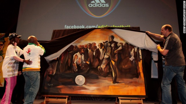SOUTH AFRICA: From left, actress Hlubi Mboya, former boxer Baby Jake Matlala and Thomas van Schaik from Adidas unveil a piece of art during a Live Quest event showcasing paintings of key moments of the 2010 FIFA World Cup at the Adidas Jo'bulani Centre in Johannesburg.