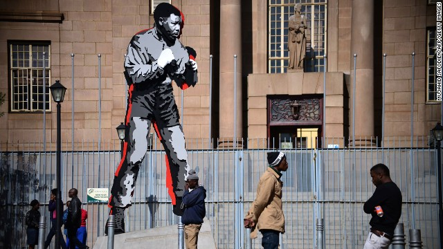 SOUTH AFRICA: People gather by a Mandela statue in downtown Johannesburg.