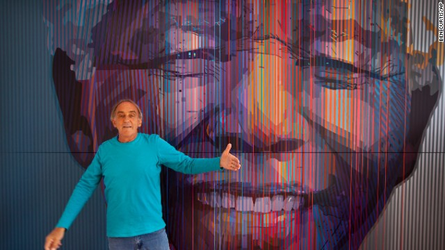 "SOUTH AFRICA: South African artist Paul Blomkamp stands in front of the giant acrylic-on-canvas painting he made of Mandela at his studio in Johannesburg. He said he was drawn to Mandela because of his ""exceptional energy."""