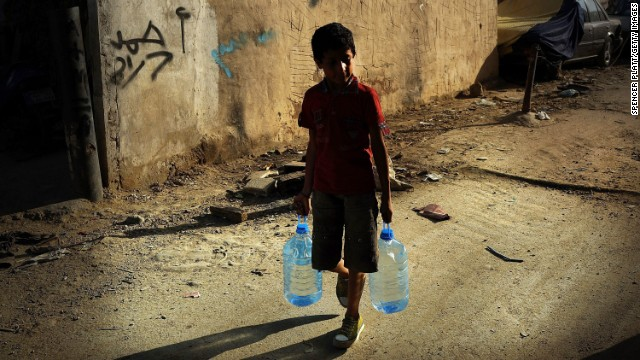 A boy walks with jugs of water on June 27 in a neighborhood in Beirut, Lebanon, with a high concentration of Syrian refugees. Since January, the number of Syrian refugees in Lebanon has more than tripled.