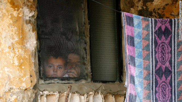 A Syrian woman and child look out of a refugee camp window on June 20 in Alman, Lebanon, after fleeing their hometown in Idlib province, Syria.