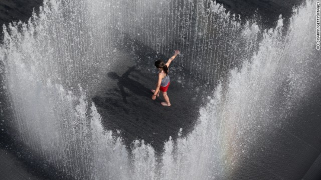 "A girl plays in the fountain called ""Appearing Rooms,"" by Danish artist Jeppe Hein, in central London on July 18. The United Kingdom is experiencing a second week of heatwave conditions."