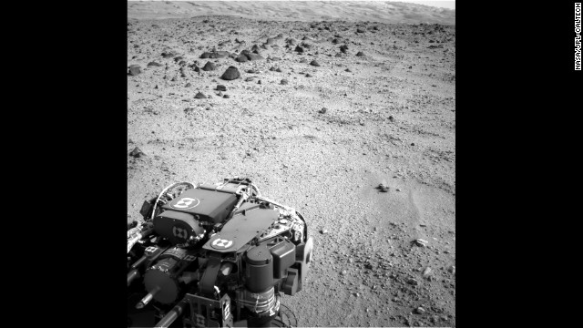 The lower slopes of Mount Sharp are visible at the top of this image, taken on Tuesday, July 9. The turret of tools at the end of the rover's arm, including the rock sampling drill in the lower left corner, can also be seen.