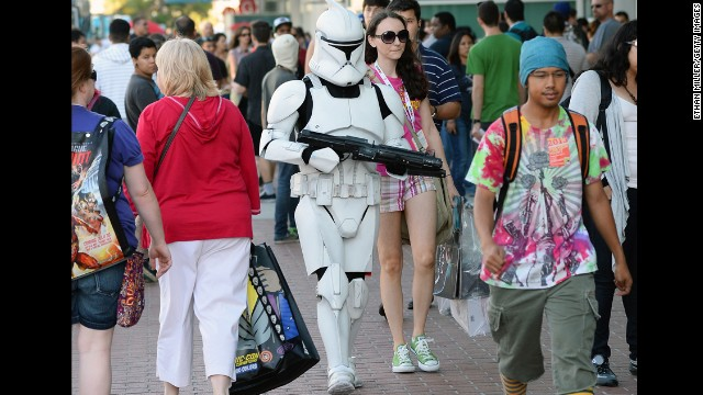 "Myke Soler walks outside the San Diego Convention Center dressed as a ""Star Wars"" stormtrooper with his wife during Comic-Con International 2013 on Wednesday, July 17, in San Diego, California. Started in 1970, the event is estimated to bring well over 100,000 attendees."