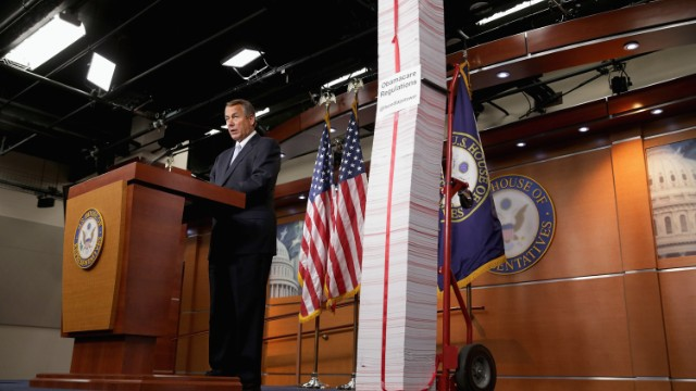 Speaker John Boehner stands next to a printed version of the Affordable Care Act on May 16 in Washington.