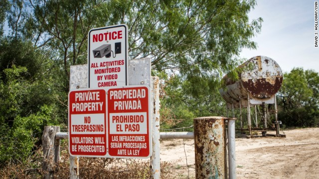 A sign warns of security cameras on a farm near the border.