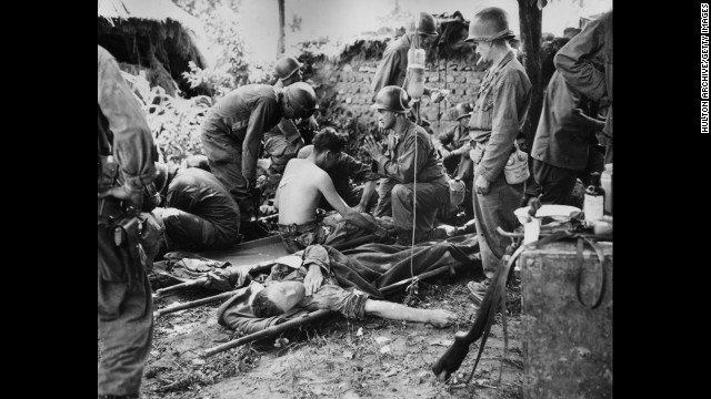 A U.S. Army chaplain prays by injured soldiers at a combat field hospital in August 1950.