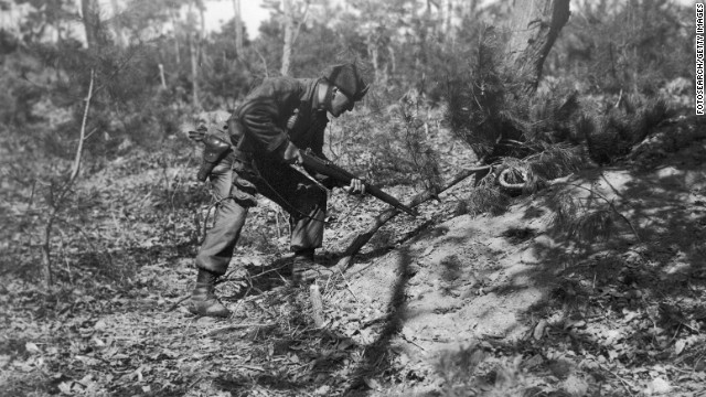An American soldier searches a foxhole for enemies in February 1951.
