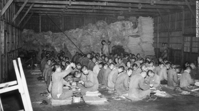 North Korean prisoners of war make baskets on the floor of a storage barn at a prison, circa 1951.