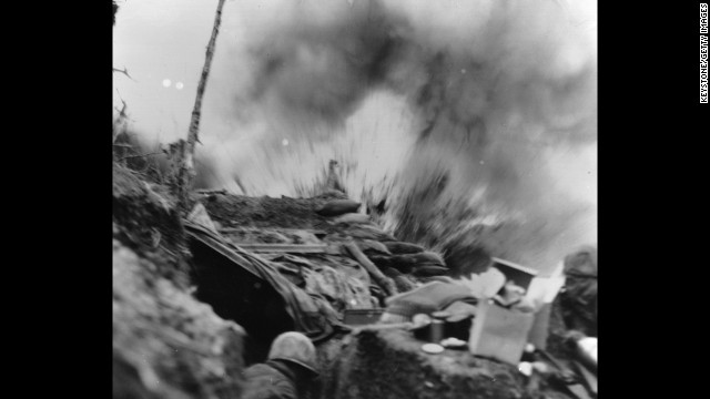 U.S. Marines duck for cover in a bunker as a shell explodes in April 1952.