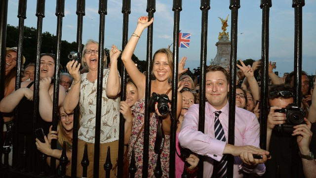 Crowds gathered outside Buckingham Palace cheer as Anderson places the birth announcement in front of the palace on July 22.