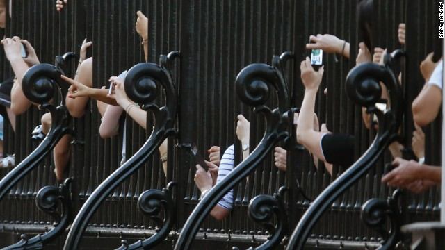 Revelers crowd against the railing of Buckingham Palace in London after an official notice proclaiming the birth was put on display on July 22.