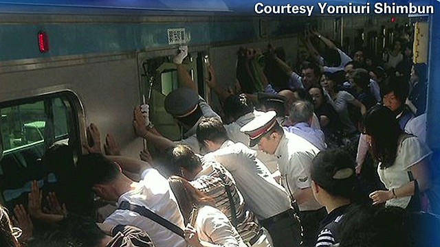 Dozens of Japanese commuters help free a woman stuck between the platform and a 32-ton train.
