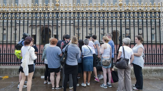 People gather outside Buckingham Palace in London on July 23 to read the notice announcing the birth of the royal baby. The news was placed in the forecourt of Buckingham Palace on July 22.