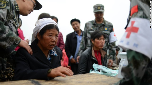 Villagers receive treatment from military medics in Yongxing, China, on July 23. Rescuers are searching for survivors in the aftermath of the quake.
