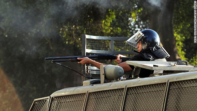 A riot police officer aims rubber bullets toward Morsy supporters in Cairo on July 22.