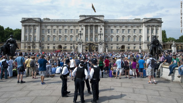 Members of the public and tourists gather outside Buckingham Palace in London in July.