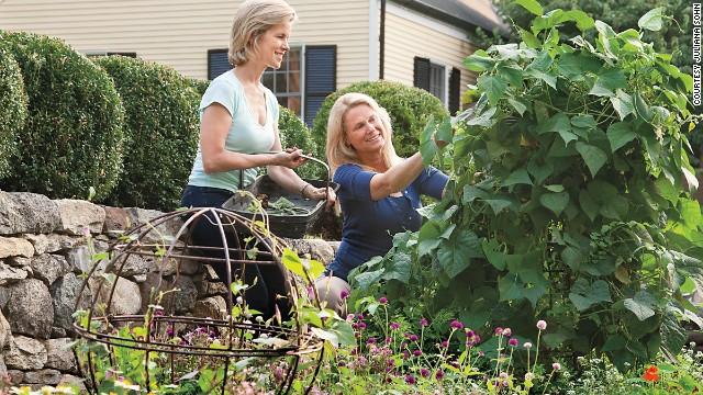 Steiner's landscape designer friend, Leslie Needham, left, helps her pick beans near the purple gomphrena.