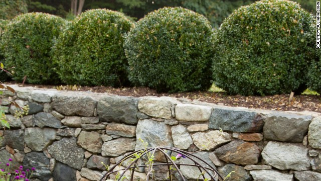 The garden is bordered on one side by simple boxwood balls, which help define the space.